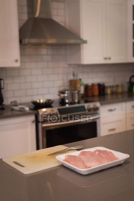 Carne em uma bandeja na bancada da cozinha em casa — Fotografia de Stock