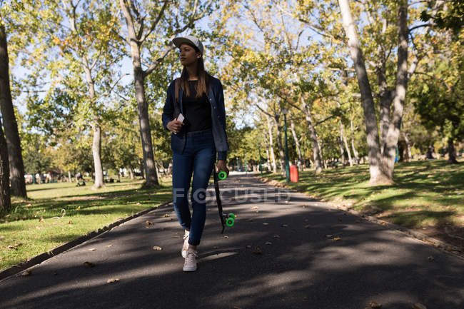 Mulher andando no parque com o skate — Fotografia de Stock