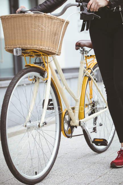 Faible section de femme à vélo à pied sur le trottoir — Photo de stock