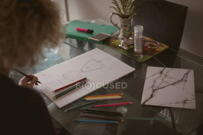 Young woman drawing a sketch at home — Stock Photo