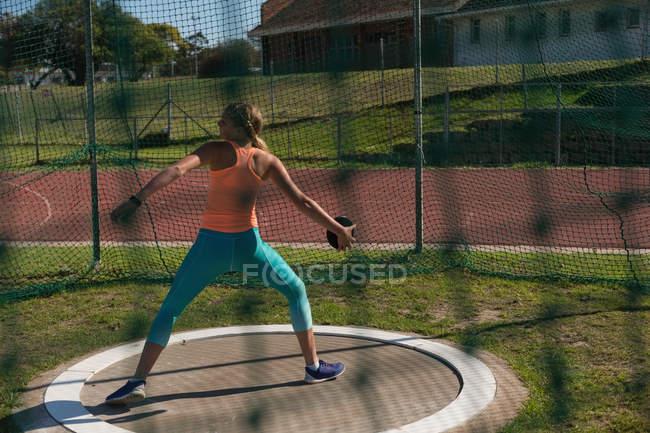 Female athlete practicing discus throw at sports venue — Stock Photo