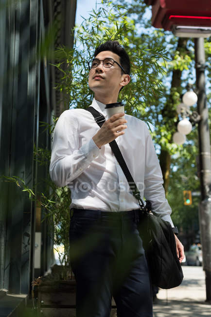 Young man with coffee cup looking at a building — Stock Photo