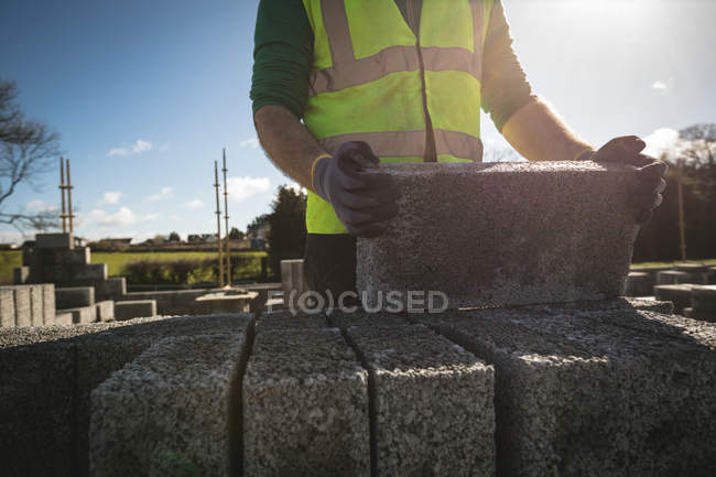 Mid section of engineer holding cement slab at construction site — Stock Photo