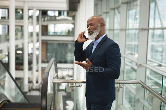 Uomo d'affari che parla al telefono in ufficio — Foto stock