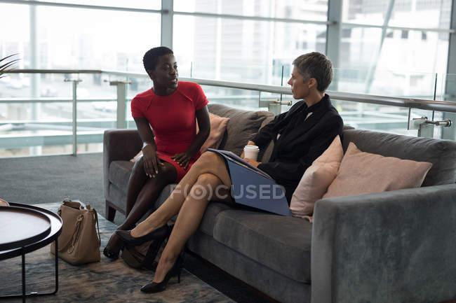 Две деловых женщины, говорящие в офисе — стоковое фото