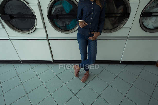 Low section of woman using her phone while waiting at laundromat — Stock Photo