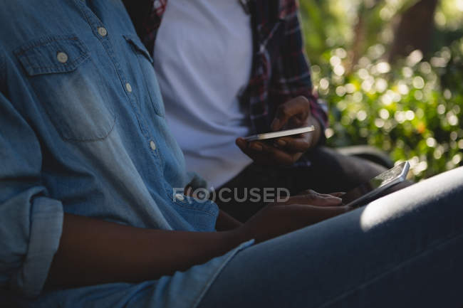 Mid section of twins siblings using mobile phone while relaxing on the bench — Stock Photo