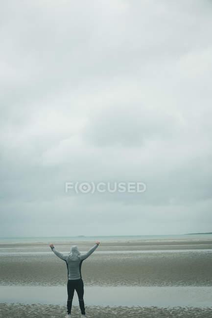 Вид сзади на счастливого человека, стоящего на пляже — стоковое фото