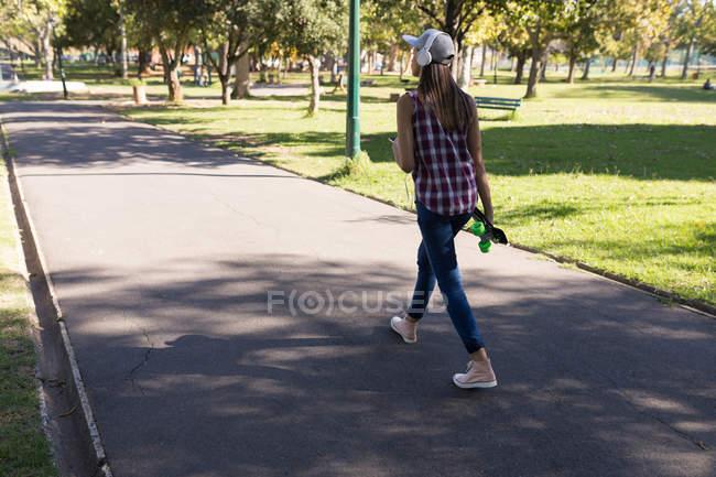 Vista traseira da mulher com fones de ouvido e patins andando no parque — Fotografia de Stock