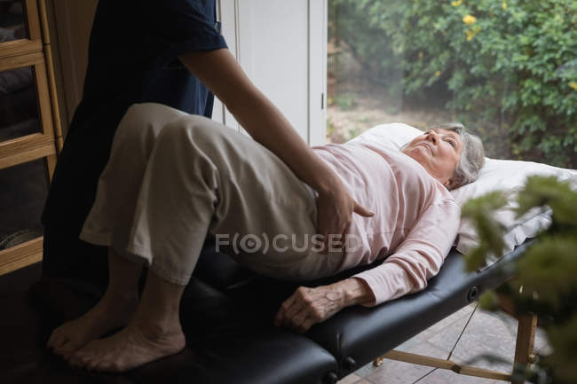 Physiotherapist giving a body massage to senior woman at home — Stock Photo
