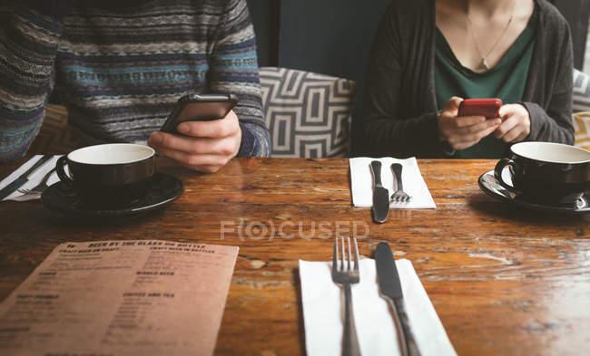Seção intermediária do casal através de telefones celulares no café — Fotografia de Stock