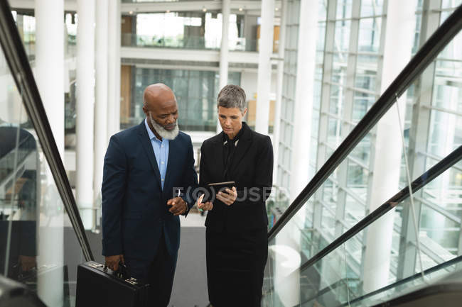 Business people discussing over a tablet while going up on an escalator in office — Stock Photo