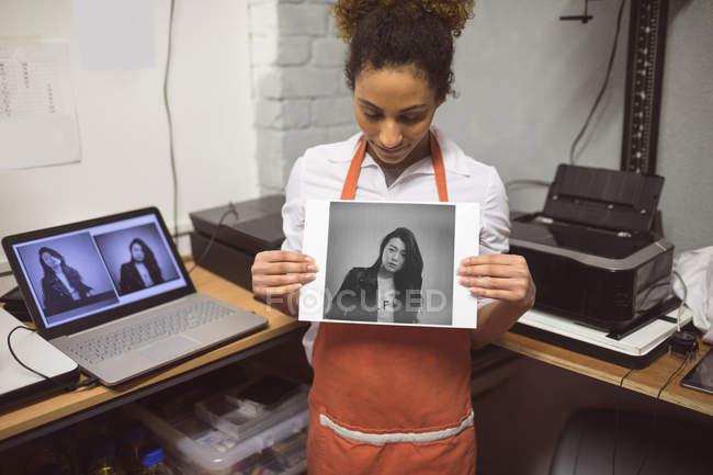 Молода жінка фотограф показ фотографій у фотостудії — стокове фото