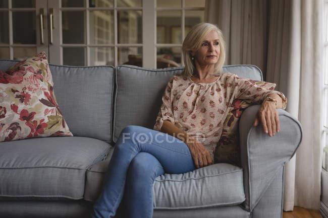 Продуманий старший жінка, сидячи на дивані в домашніх умовах — стокове фото