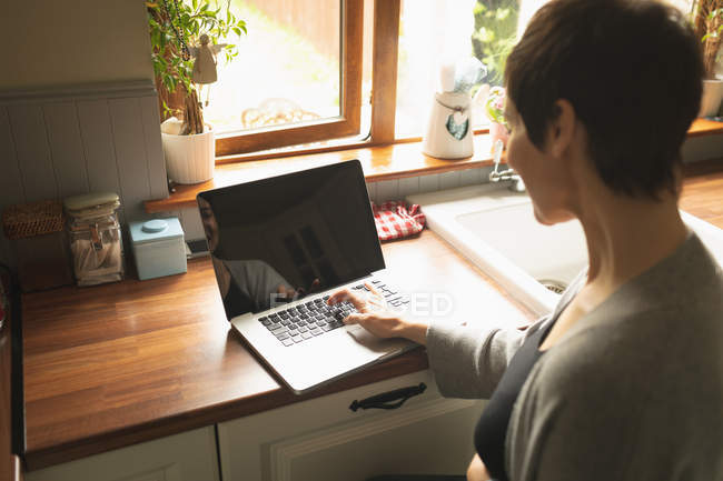 Pregnant woman using laptop in the kitchen at home — Stock Photo