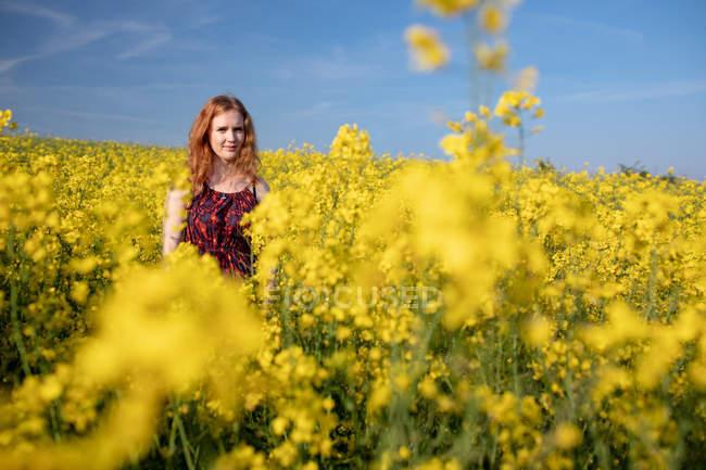 Mulher de pé no campo de mostarda em um dia ensolarado — Fotografia de Stock
