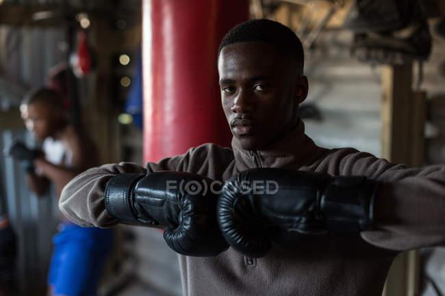 Retrato de boxeador masculino em pé com luvas de boxe no estúdio de fitness — Fotografia de Stock