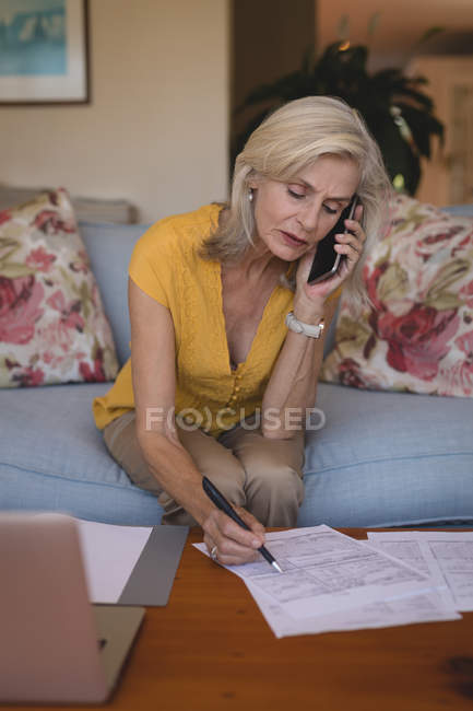 Senior woman talking on mobile phone while checking bills at home — Stock Photo