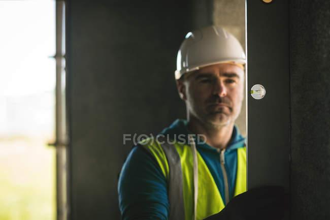 Крупным планом инженера, делает проверку уровня на стене на строительной площадке — стоковое фото