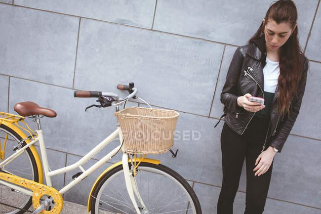 Bella donna che utilizza il telefono cellulare contro muro — Foto stock