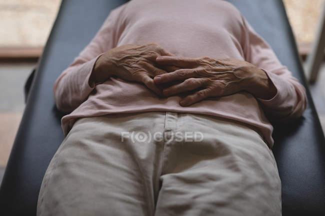 Крупным планом старший женщина, лежа на кровати с руки на животе — стоковое фото