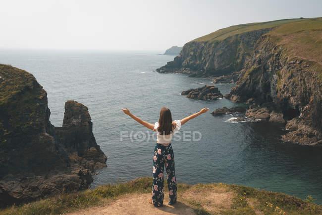 Заднього вигляду жінку, що стоїть на краю скелі з її рук поширення — стокове фото