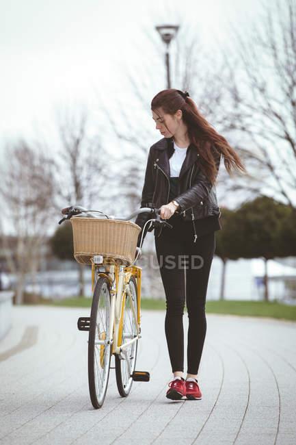 Красива жінка з велосипеда, йдучи по тротуару — стокове фото