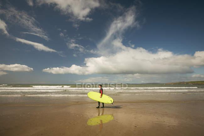 Серфер з дошки для серфінгу стояти під Біч у сонячний день — стокове фото