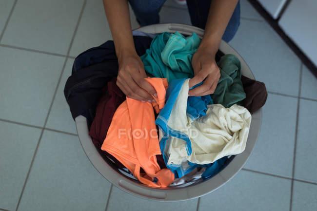Крупным планом женщины, сортировка одежды в корзину Прачечная — стоковое фото