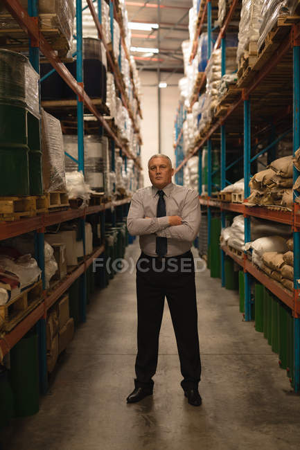 Male manager standing with arms crossed in warehouse — Stock Photo