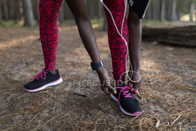Low section of female athlete tying her shoe lace in the forest — Stock Photo
