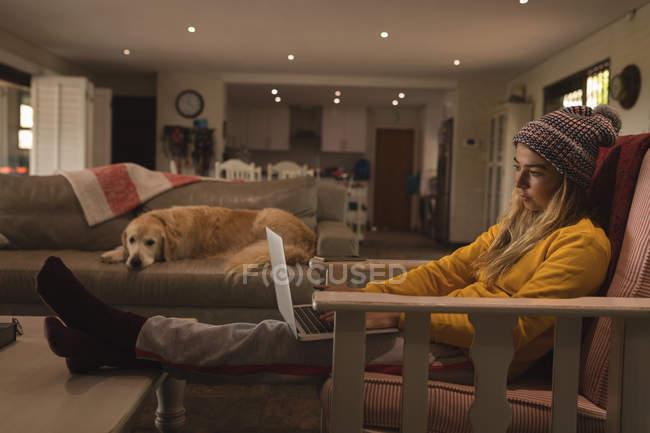 Mädchen mit Hund benutzt Laptop im heimischen Wohnzimmer — Stockfoto