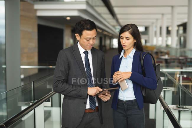 Homme d'affaires et femme d'affaires discutant sur une tablette numérique au bureau — Photo de stock