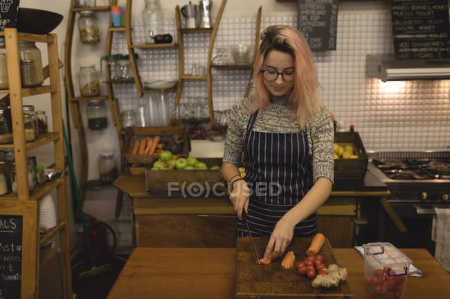 Молодая женщина режет овощи на доске — стоковое фото