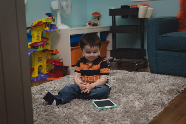 Adorabile ragazzo seduto con tablet digitale a casa — Foto stock