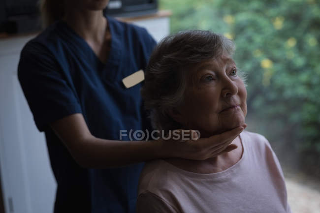 Physiotherapist giving a neck massage to senior woman at home — Stock Photo