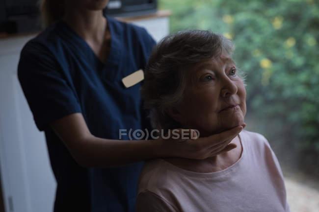 Fisioterapeuta dando uma massagem no pescoço para a mulher idosa em casa — Fotografia de Stock