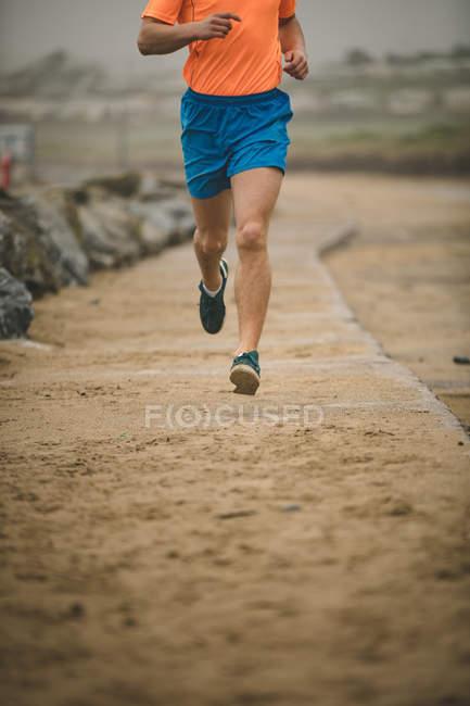 Низкая часть человека бегает по набережной на пляже — стоковое фото