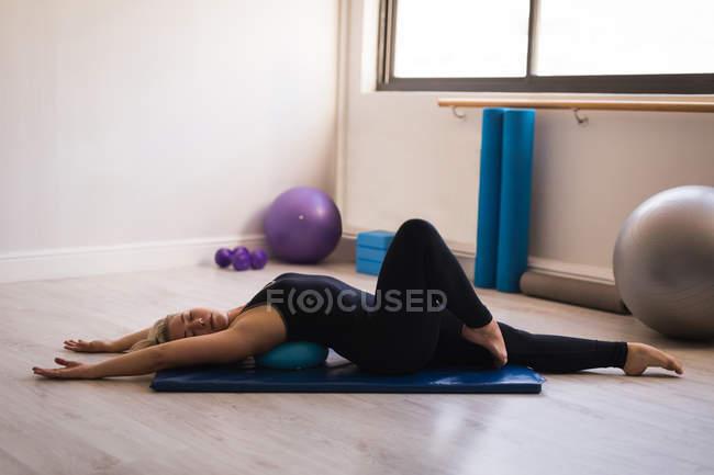 Женщина выполняет упражнения на растяжку в фитнес-студии — стоковое фото