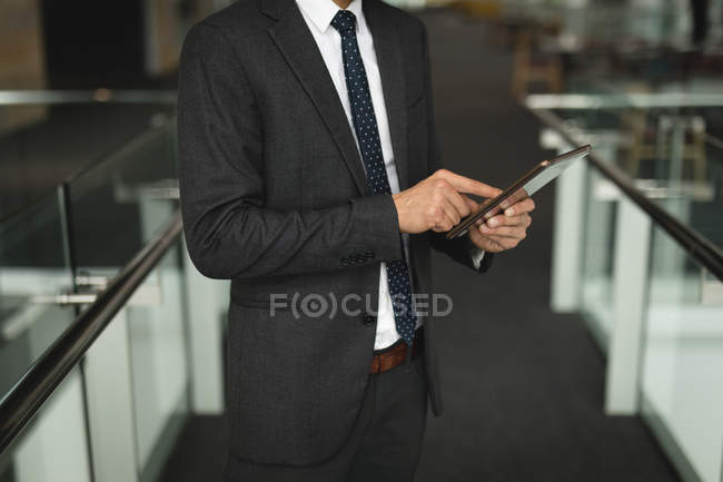 Sezione centrale dell'uomo d'affari che utilizza un tablet digitale in ufficio — Foto stock