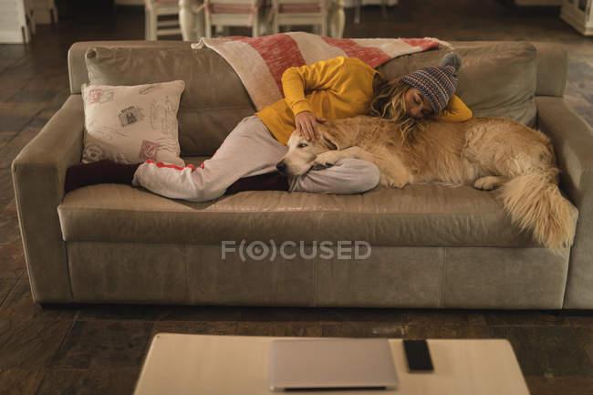 Mädchen mit Hund schläft zu Hause im Wohnzimmer — Stockfoto