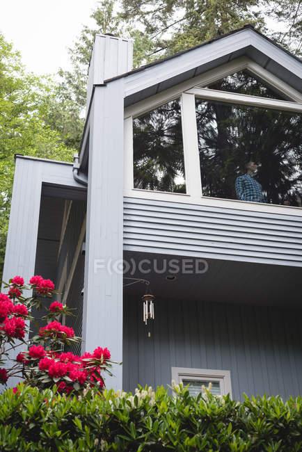 Hombre pensativo de pie junto a la ventana en casa - foto de stock