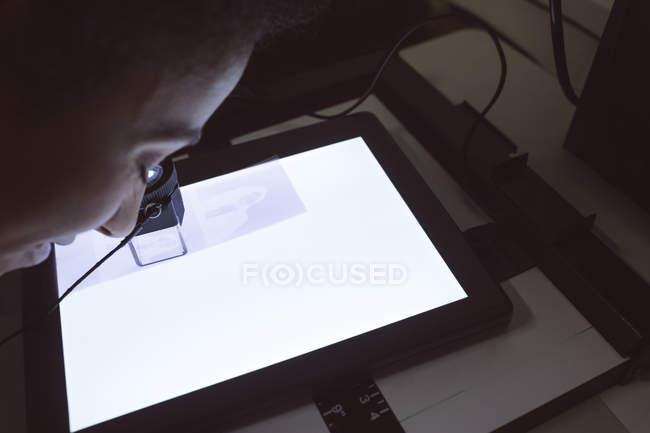 Женщина-фотограф с помощью карманного лупы в фотостудии — стоковое фото