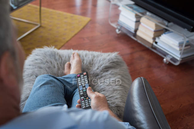 Man changing channels while watching television in living room at home — Stock Photo