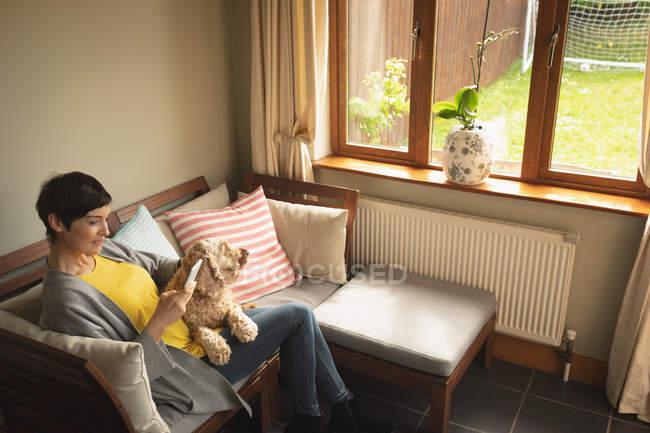 Femme utilisant un téléphone portable avec chien sur canapé dans le salon à la maison — Photo de stock