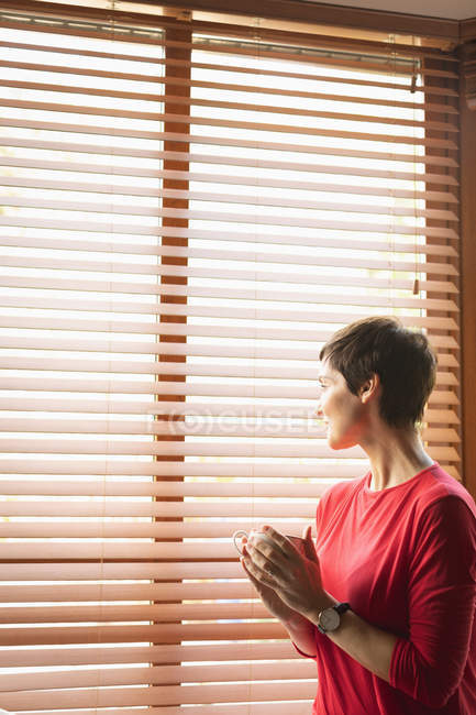 Woman looking through window while having coffee in living room at home — Stock Photo