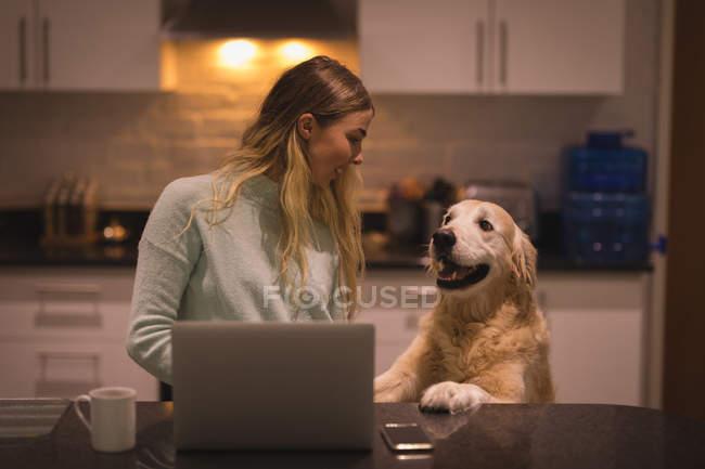 Mädchen benutzt Laptop mit Hund in Küche zu Hause — Stockfoto
