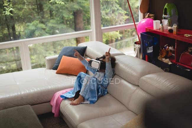 Девушка с гарнитурой виртуальной реальности на диване дома — стоковое фото