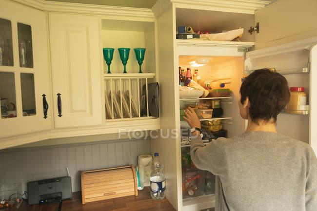 Vue arrière de la femme regardant dans le réfrigérateur pour la nourriture à la maison — Photo de stock