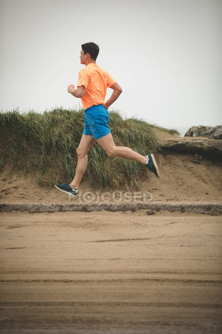 Young man jogging on boardwalk at beach — Stock Photo